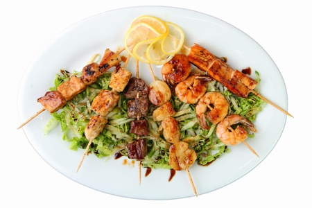 skewers of different meats on a wooden skewers on a white platter with lemon on white background