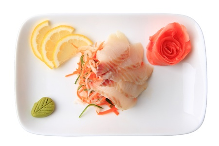 sashimi izumitai with slices of grouper, lemon lobules, ginger and wasabi on rectangular dish isolated on a white background. top view. photo