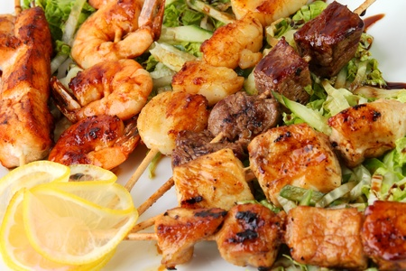 chicken kebab: skewers of different meats on a wooden sticks on a white platter with lemon