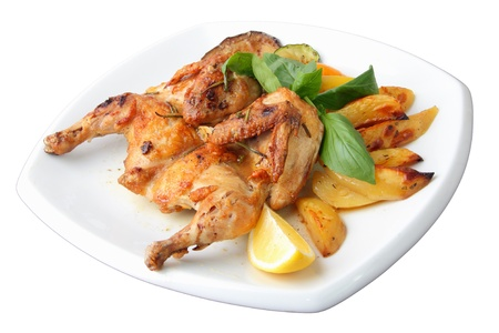 crispy: small grilled chicken with vegetables on a white dish isolated over white background. Side view.