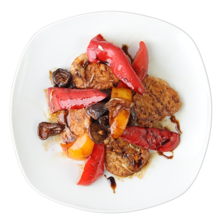 marinated pork with shiitake mushrooms and sweet peppers on white dish isolated on a white background  Top view  photo