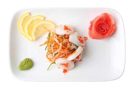 hotate: sashimi hotate with slices of scallop, lemon lobules, ginger and wasabi on rectangular dish isolated on a white background. top view.