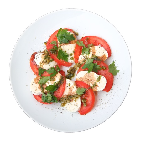 tomato slices: slices of mozzarella and  tomato with fresh basil and capers sauce on white dish, top view.