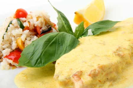 Scottish salmon steak in a yellow creamy saffron sauce with rice garnish on a white background