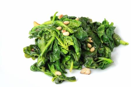 espinaca: la espinaca verde intenso con frutos secos de ajo y el pino sobre fondo blanco Foto de archivo