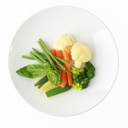 steamed vegetables of yellow, green and orange colors on white dish isolated on a white background.background