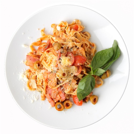Pasta fettuccine with tomato, olives and bacon on white round dish isolated on a white background. Top view.