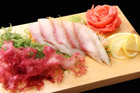 sashimi hamachi with slices of yellowtail, lemon lobules, ginger wasabi, red and green algae on rectangular board isolated on a black background photo