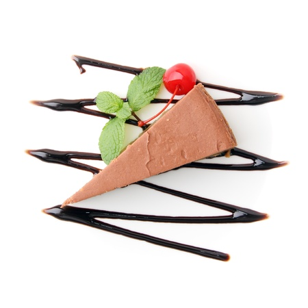 piece of chocolate cheesecake with mint twig and cherry on white background. Top view. Stock Photo