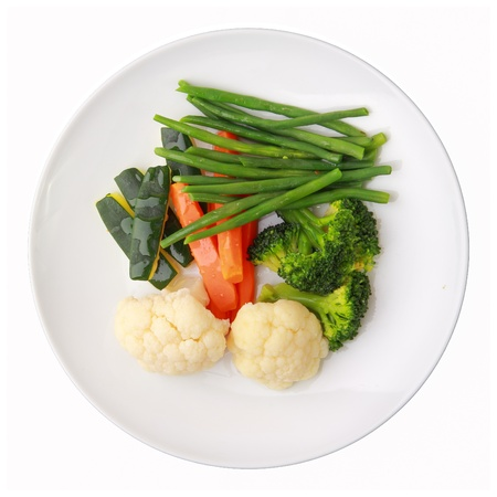 steamed vegetables of yellow, green and orange colors on white round dish isolated over white background. top view. Standard-Bild