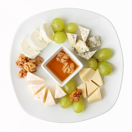 A dish with four kinds of cheese, grapes, walnuts and honey. Top view. Standard-Bild