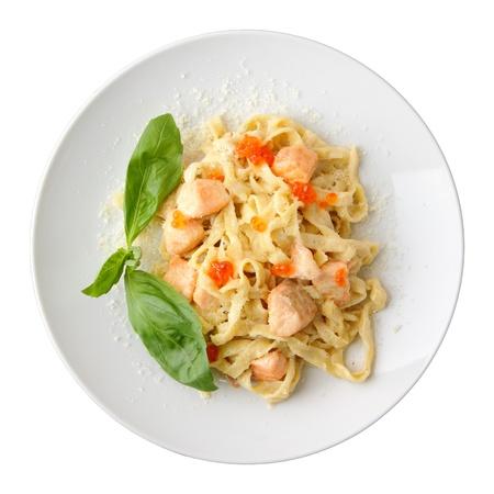 Fettuccine di pasta con salmone e caviale su un piatto bianco isolato su uno sfondo bianco. Vista dall'alto. Archivio Fotografico