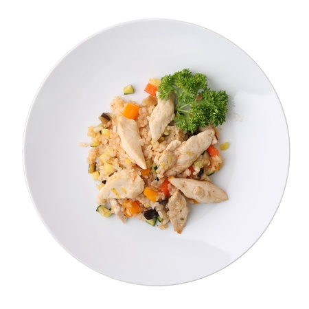 Rice with vegetables and pieces of chicken on white round dish isolated on a white background. Top view. Standard-Bild