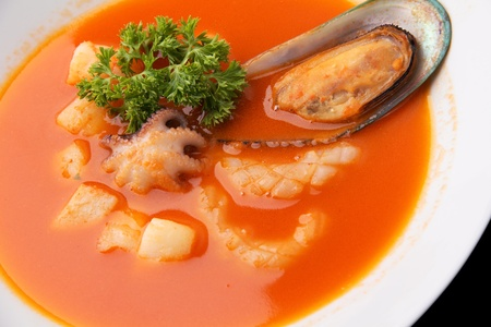 seafood soup: red  soup with seafood in a white dish on a white background closeup Stock Photo