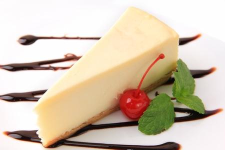 stuk van vanille cheesecake met kersen en munt blaadje op een witte achtergrond Stockfoto