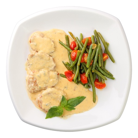 Medallions of veal in a creamy sauce with mushrooms and marinated vegetables on a white background. Top view.