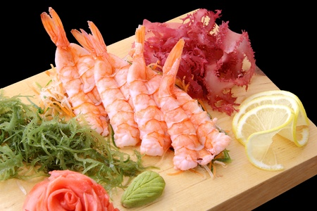 sashimi eb with shrimps, lemon lobules, ginger, wasabi, red and green algae on rectangular board isolated on a black background photo