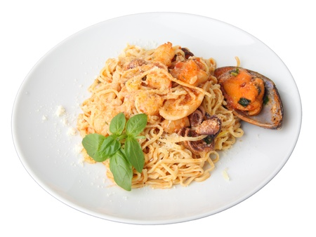noodles tagliolini with seafood and basil twig on a round white dish isolated on a white background.