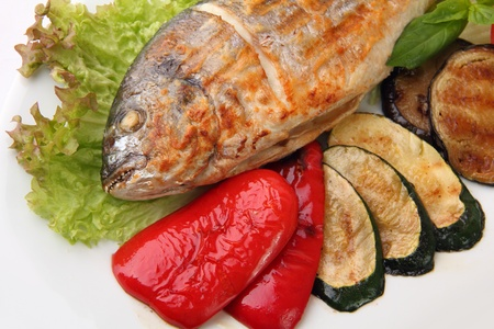 close up grilled whole Dorado with different vegetables on white background photo