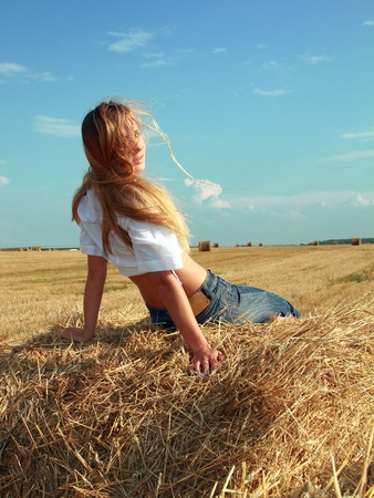 Young attractive girl sit on a bale of yellow straw at field photo