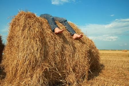young barefoot girl lies on roll of dry hay under clear sky. Only feet are visible.  photo