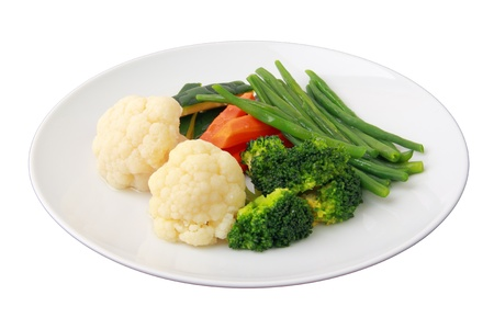 assorted steamed vegetables of yellow, green and orange colors on white round dish isolated over white background. Side view.