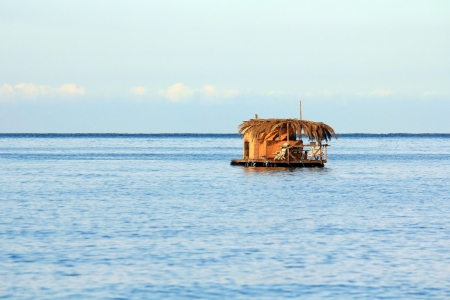 Single houseboat on a small raft at open sea under blue clear sky photo