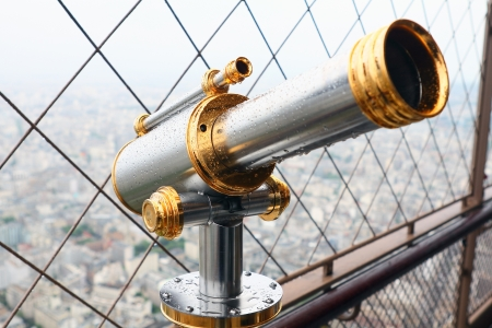 Telescope mounted on top of the Eiffel Tower observation deck. It is wet after rain. View to Paris. photo