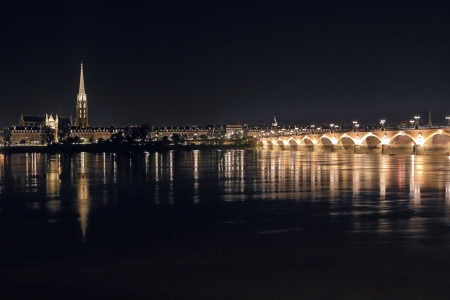 Night panorama of Bordeaux. View from behind river to The illuminated Peter Bridge and cathedral