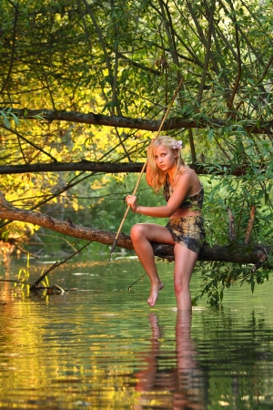 jungle girl: cute savage girl with gaff sits on a branch above water surface
