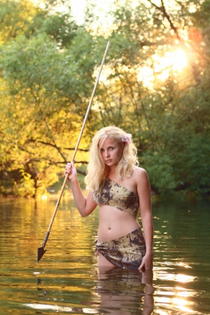 cute savage girl with gaff stands in the water of river photo