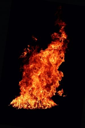 Large orange flame isolated over black background photo