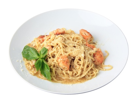 pasta tagliolini with pesto and shrimps on a white dish isolated on a white background  Side view