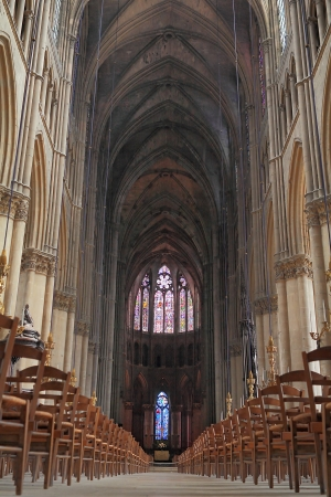 interior of Reims cathedral with dark ceiling and old chairs