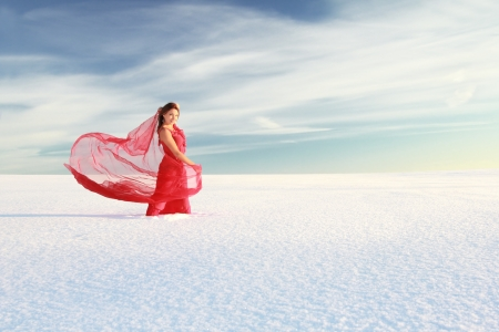 Young woman in red dress with translucent shawl in the snowy wilderness under blue sky photo