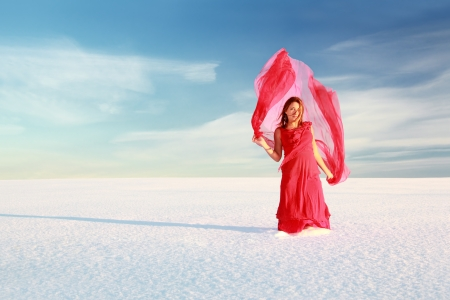 Young woman in red dress with translucent shawl Picked up by the wind in the snowy wilderness under blue sky. Stock Photo