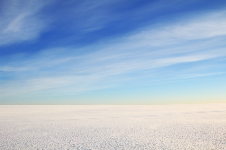 boundless snow desert. Cirrus clouds are in the sky. Stock Photo
