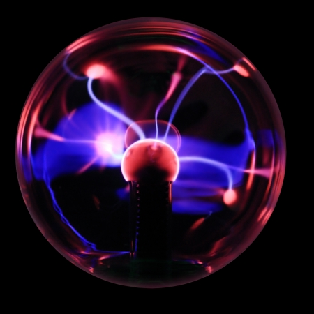 captivate: Plasma ball souvenir with magenta-blue lightnings isolated on a black background. Stock Photo