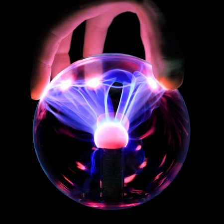 magnetism: Hand holds a plasma ball with magenta-blue flames isolated on a black background. Blue flames directed to the fingers.