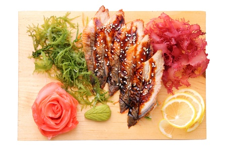 sashimi unagi with slices of eel, lemon lobules, ginger, wasabi, red and green algae on rectangular board isolated on a white  photo