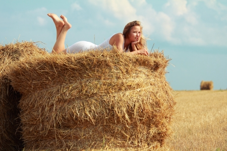 young caucasian girl in white transparent dress lies on bale of straw over the cloudy sky background photo