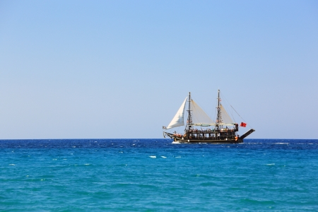 brigantine: single pirate sailing ship at open sea under clear sky