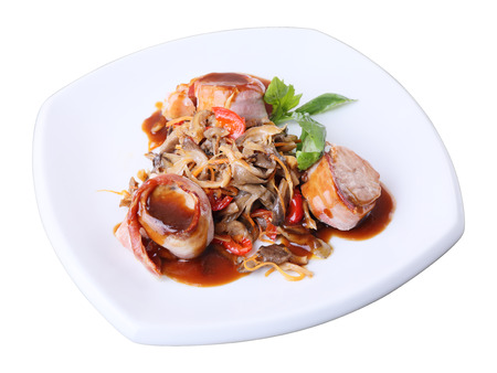 Three medallions of pork wrapped in bacon with oyster mushrooms and sauce on a white dish isolated over white background