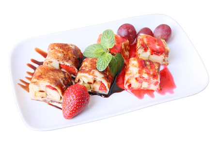 Sweet fruit roll with Banana, strawberry and grapes, wrapped in pancake under chocolate sauce and red berry jam on white rectangular dish isolated on a white background photo