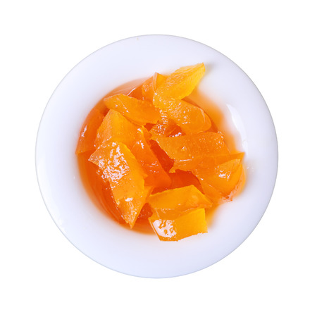 deep orange: Chips of deep orange apricot mustard in small white round dish isolated on a white background
