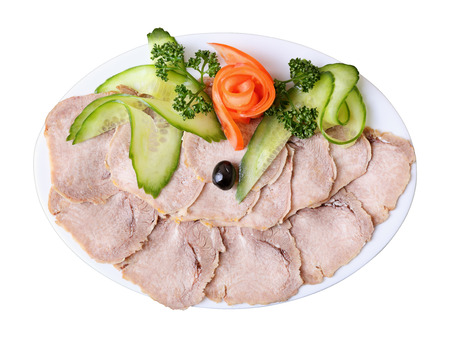 slices of tongue with greens and vegetables  on  white elliptical dish photo