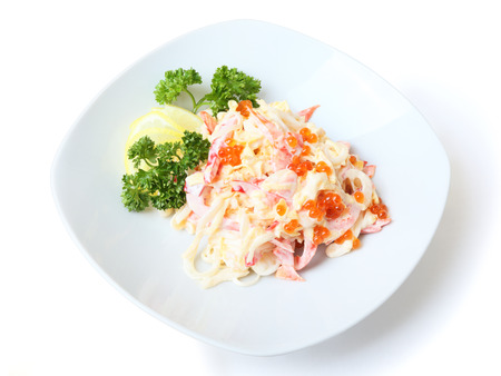Nemo salad with squid, pepper, lollo Rosso salad, Japanese omelet and mayonnaise on white dish. There is red caviar on it. Side view.