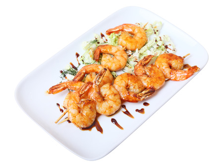 two skewers of shrimps on a white rectangular platter photo