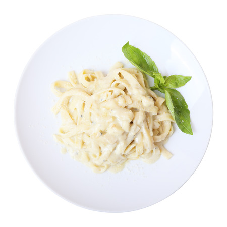 Pasta fettuccine with melted cheese on a white round dish isolated on a white background. Top view.