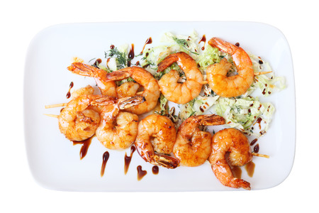 two skewers of shrimps on a white rectangular platter isolated on white background. Top view. photo